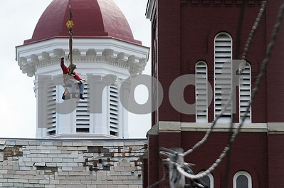 Robert Layman / Staff Photo A repairman from the Vermont Roofing Company, Inc. gives a crane signal while being hoisted up to the First Baptist Church's slate roof Wednesday morning.