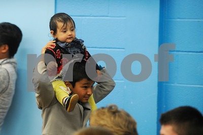 Robert Layman / Staff Photo  A young Nabina Tiwari is carried by a family member during her aunt's naturalization ceremony at Neshobe School in Brandon.