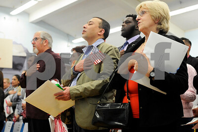 Robert Layman / Staff Photo  New citizens say the Pledge of Alligence during the end of their naturalization ceremony at Neshobe School in Brandon Wednesday.