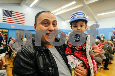 Robert Layman / Staff Photo  Karna Tiwari, left, holds is daughter Nabina as she eats a strawberry while they wait for the Naturalization Ceremony to commence at Neshobe School Wednesday night. Karna was there to support his sister who became a citizen Wednesday after migrating from Bhutan.