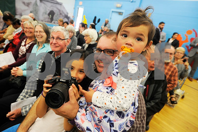 Robert Layman / Staff Photo Pria Byrom, left, her father Jed, center and youngest sister Zora wait for Terry to be announced during the naturalization ceremony at Neshobe School in Brandon Wednesday afternoon.
