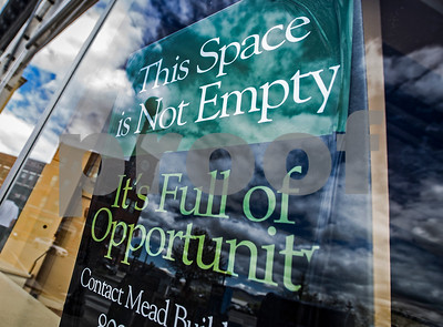 """Robert Layman / Staff Photo  A sign reading """"This space is not empty, it's full of opportunity,"""" is posted in a vacant commercial space on the ground level of the Mead Building."""