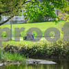 Robert Layman / Staff Photo A man mows the grass alongside the banks of the Neshobe River in Brandon Tuesday.