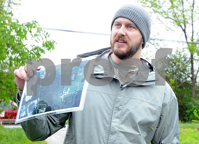 Robert Layman / Staff Photo Brad Wilson, consultant from Alko Renewable Energy Limited, holds up map of the proposed solar panel project on Cold River Road in Rutland Town during a project tour Monday afternoon.