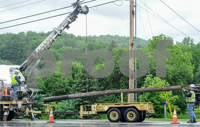 Robert Layman / Staff Photo A work crew from Fair Point Communications loads a telphone pole onto a trailer off the side of Route 4 Business in Center Rutland Tuesday morning.