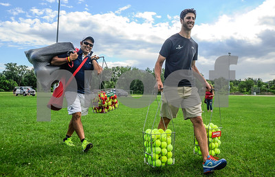 Robert Layman / Staff Photo Dan Doenges, right, owner of Vermont Sport and Fitness, carries in tennis balls to the courts at Meadow Park Tuesday afternoon with tennis instructor Akahnaton Aguilar and Rob Purdy, not pictured, for the Rutland Recreation Department's Tennis Summer Nights program.