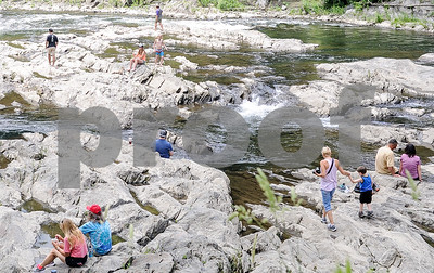 Robert Layman / Staff Photo As summer begins heating up the region people often look for a nice water source to cool off by. Seen here on Sunday, groups of people make their way across the bottom of Quechee Gorge for some outdoor adventure.