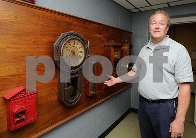 """Robert Layman / Staff Photo Although Chief Lovett is hopeful of the future for the Rutland City Fire Department, he is still facinated by the past and how it worked in the """"old days."""" An switch board displays old relics from the early 201th century of fire fighting in the city. From  left to right: A telegraph would trip a clock, so the fire fighters knew what time the call came in, and then a device would open the doors so the horses could run to their post. Finally, the telegraph would send a signal to  a box with digits displaying the digits which identified the location of the alarm."""