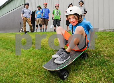 Robert Layman / Staff Photo Keaton Tarbell, 9, rolls down the hill on a dirt board beside the Flip Side Skate Park during summer camp Thursday morning.