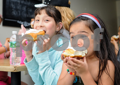 Robert Layman / Staff Photo Willa Seo, left, and Briana McFarren dig into the donuts.