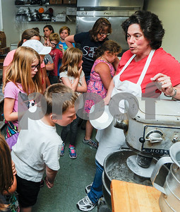 Robert Layman / Staff Photo Lynn Manney, owner of Jones Donuts & Bakery shows kids from the Wallingford Summer Recreation Program how batter for donuts is made at her bakery Thursday afternoon. Manney taught the two-dozen children about donut making for the camps unit on food.