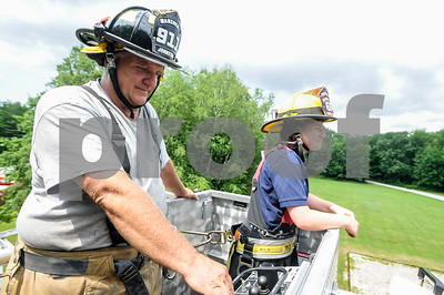 Robert Layman / Staff Photo Marc Johnston, center, of the Manchester Fire Department brings cadet Ahna Perry, 15, of Proctorsville up 95ft in the air on the ladder truck at the Vermont Fire Acadedmy in Pittsford Friday morning. Johnston and other fire fighters from different parts of the state volunteered their time this week to help train 21 youth at the acadedmy in  basic fire fighting and emergency service skills.