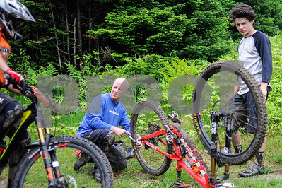 Robert Layman / Staff Photo Although highly competitive, the mountain biking community is very helpful. Seen here another racer stops during practice to ask John Beaupre, left, of Sutton, MA, and his son Max if they need help with a leaking tire. John is competing in the men's 50+ division while Max is in the under 18.
