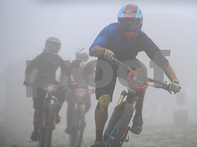Robert Layman / Staff Photo Bikers take off from the foggy Killington peak Friday afternoon during a round of practice.