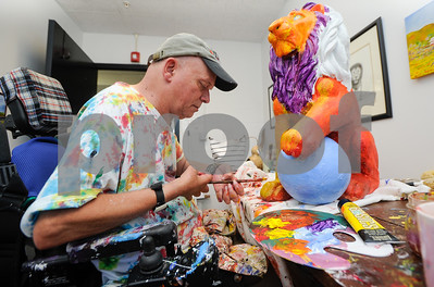 """Robert Layman / Staff Photo Dan Gilman, artist in residence at the Compass Arts Center in Brandon, paints a lion statue in his studio Wednesday morning. """"I like to repurpose things,"""" Gilman said about the lion, which he purchased at an auction."""