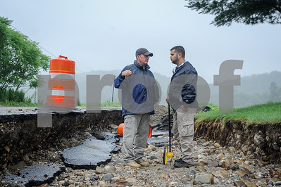 Robert Layman / Staff Photo Keith McGinnis, left, and Seth Grill of FEMA conduct their assessment alongside a washed out section of Newton Road in Brandon Thursday morning.