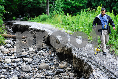 Robert Layman / Staff Photo Seth Grill, of the FEMA damage assessment team, walks down the remnants of West Hill Road, of which over 1000 feet were damaged due to heavy flooding July 1, 2017. This photo was taken July 13, 2014.