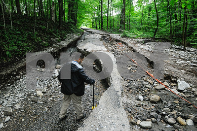 Robert Layman / Staff Photo Seth Grill, right,  of the FEMA damage assessment team,  takes depth estimates alongside the remnants of West Hill Road, of which over 1000 feet were damaged due to heavy flooding July 1, 2017. This photo was taken July 13, 2014.