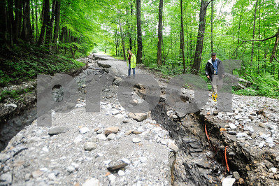 Robert Layman / Staff Photo Seth Grill, right,  of the FEMA damage assessment team,  walks down the remnants of West Hill Road, of which over 1000 feet were damaged due to heavy flooding July 1, 2017. This photo was taken July 13, 2014.