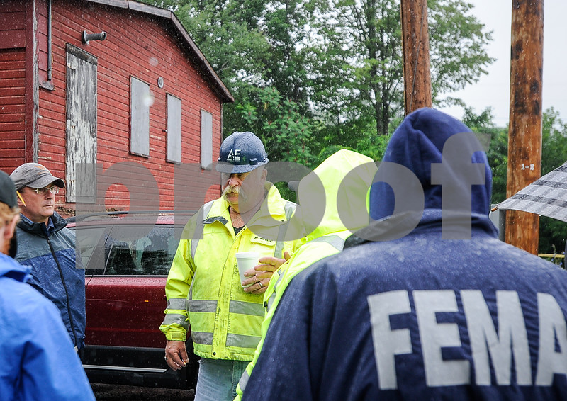 Robert Layman / Staff Photo Daryl Burlett, center, Brandon Public Works Director talking with Vermont State officials and FEMA asessors at the Newton Road flood site Thursday morning.