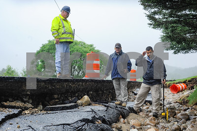 Robert Layman / Staff Photo Keith McGinnis, center, and Seth Grill, right of FEMA conduct their assessment with Daryl Burlett, left, Brandon Public Works Director, alongside a washed out section of Newton Road in Brandon Thursday morning.