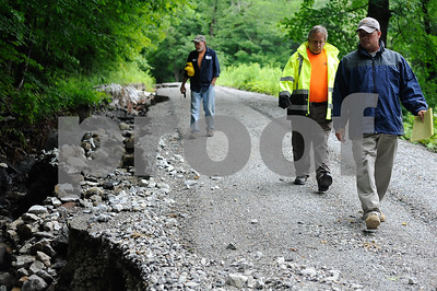 Robert Layman / Staff Photo Keith McGinnis, right, FEMA conduct their assessment with Phil Baker, center,Wallingford Road Comissioner, and Steve Lanfear, left, alongside a washed out section of Newton Road in Brandon Thursday morning.