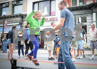 Robert Layman / Staff Photo Joel Flewelling spots his daughter Brooke as they cross the slackline during Rutland's Friday Night Live event.