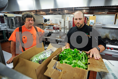 Robert Layman / Staff Photo It's Monday morning and Sean Miller, right, Food Service Director for Rutland City Public Schools, has 350 meals to make for the state's Summer Meals program at the high school. This morning's lunch was a bit different, as it marks the first dilevery of 9 pounds of farm fresh lettuce from The Vermont Farmers Food Center's Food Procurment Program, brought by Greg Cox, VFFC President. According to Miller, he'll use the lettuce for sandwiches that are dilivered to 7 schools in the city.
