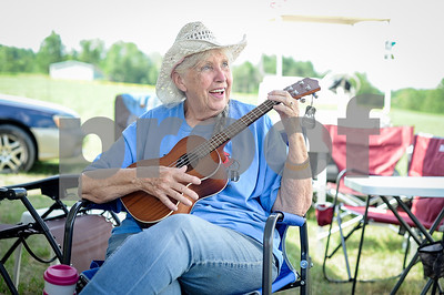 Robert Layman / Staff Photo Annie Lees, of Shrewsbury,  picks out a tune on her new ukulele at the Danby Olde Country & Bluegrass Festival Wednesday afternoon. Lees and her husband Rick have been atendees since the first one a decade ago.