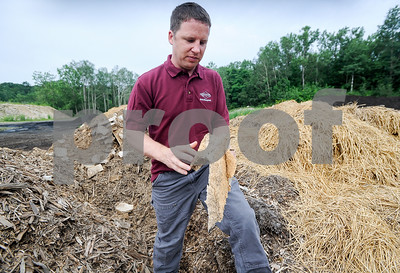 Robert Layman / Staff Photo Trevor Mance, founder of TAM's Waste Management Inc., stand between piles of composted wood chips, hay and a mushroom-based material at the company's compost division in Bennington. Seen here he's holding pieces  once used for packing materials made by NY-based company Ecovative products, which uses mushroom roots and organic matter that grows into a durable plastic alternative. This photo was taken Thursday, July 20, 2017.