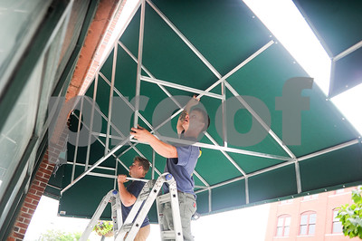 Robert Layman / Staff Photo Jarad Milot, right, and Aaron Doney of Otter Creek Awnings hoof a 150lb section of awning up their stepladders and onto the side of the ASA Bloomer building on Merchants Row Tuesday afternoon.