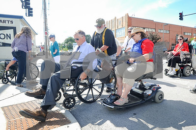 "Robert Layman / Staff Photo Wednesday July 26, 2017 marked the 27th anniversary the Americans With Disabilities Act was signed. Members of the Rutland City government met with local disability advocate groups to tour around the city in an event hosted by the Vermont Center for Independent Living. Seen here, Maylor Dave Allaire, left, gets stuck on a ""curb cut,"" an area of sidewalk that is not flush wtih the road, which can cause a wheel chair to be stuck on the side. Allaire and 3 Alderman toured trouble spots in the city with disabled residents. To Allaire's right is Rose Denardo and int he center is Gary Donahue."