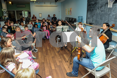 "Robert Layman / Staff Photo Gabo Lewis, right, viola player, teaches children at the Rutland County Boys & Girls club about his stringed instrument during a performance with other members of the Killington Music Festival. The group was about to play Motzart's ""The Hunt."""
