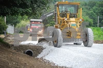 "Robert Layman / Staff Photo A road graders from Markowski Excavating smooths out a pile of new gravel on Newton Road. Residents along the road have recieved new 18"" culverts underneath their driveway, seen here in the ditch on the left."