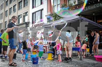 Robert Layman / Staff Photo Tom Poole, left, makes a large bubble using sticks and rope outside the Wonderfeet Kids Museum tent on center street. According to the Guinness Book of World Records, the longest soap bubble was 166ft long and created by Fan Yang of Canada during a Guinness World Record Special in Beijing, China on 17 November 2009.
