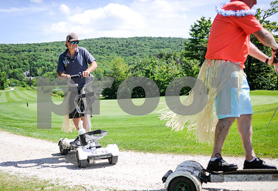 Robert Layman / Staff Photo John Hobbs, left and members of his team head to the next hole on their golf boards while sporting Hawaiaan skirts and leas during the  Burton Not So Chilly fundraiser tournament at Killington Resort Friday afternoon. Event organizer Shaun Cattanach, not pictured, said after admissions, raffles, and mulligan purchases, the event should bring in over $4,000 for the Chill Foundation -- a non-profit youth development program that aims to help kids from 10-18 be removed from troubled circumstances and reach their full potential through snow sports.