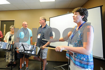 Robert Layman / Staff Photo Cohen, right, sests a tempo with drum sticks for the class to follow.