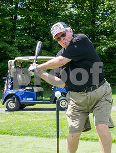 Robert Layman / Staff Photo Bob Osnoe takes a swing at a ball on an upside down golf club that's staked into the ground.
