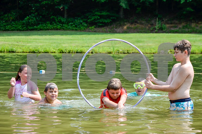 Robert Layman / Staff Photo Hunter Kehoe, center, dives through a hoop with other members of the Pittsford Recreation Area day camp Friday afternoon. The camp celebrated Friday as it's last day, and the hot humid weather was perfect for it.