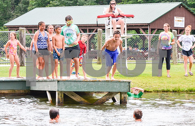 Robert Layman / Staff Photo Jasper Nadeau, center, dives off the dock at the Pittsford Swim Area Friday afternoon. Nadeau and the other swimmers were part of the Pittsford Recreational Day Camp which celebrated its final day Friday August 4, 2017.