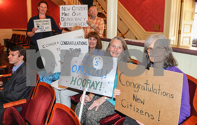 Robert Layman / Staff Photo Laura Evans, right, and other members of People Power, an ACLU organization, wave signs during the naturalziation ceremony Thursday at the Paramount Theatre in Rutland.
