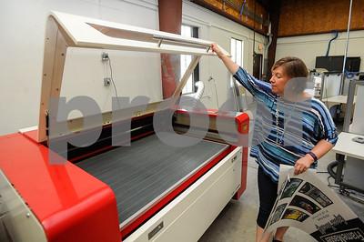 Robert Layman / Staff Photo Karen McCalla opens the hood to the MINT's 120W laser cutter.