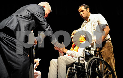 Robert Layman / Staff Photo Chitra Khar Dhakal, center, shakes hands with David Demag, a US Marshal, as he's pushed by his son Som during his naturalization ceremony at the Paramount Theatre in Rutland Tuesday afternoon. The Dhakals are formely of Bhutan but now live in Burlington.