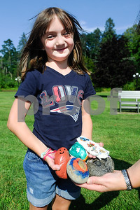 Robert Layman / Staff Photo Cassie Baker and her mother Julie hold out a handful of rocks they've collected. According to the Bakers, the rocks can be found and released. When asked if there's a special rock in the mix, Julie Baker said Boston Red Socks rocks are highly regarded.