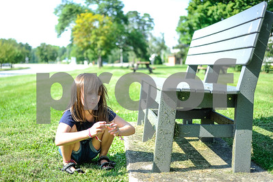 Robert Layman / Staff Photo Cassie Baker, 6, of Proctor finds a rock underneath a park bench on the town green.