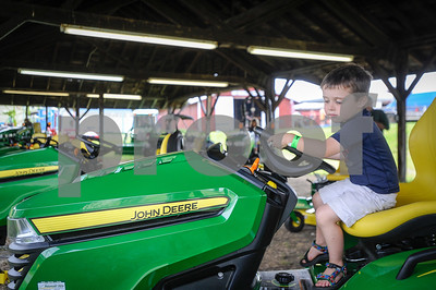 Robert Layman / Staff Photo Ethan French, 3, of Wallingford, watches the wheels turn on a John Deere tractor as he plays on it during the opening day of the Vermont State Fair Tuesday in Rutland.