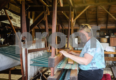 Robert Layman / Staff Photo Mary Mitiguy, of Ira, makes a rug using cut up t-shirts on an old barn loom Tuesday at the Vermont State Fair. Mitiguy said the loom dates back 200 years and mostly makes rugs for as a hobby but sometimes donates them to non-profits for their silent auction fundraisers.