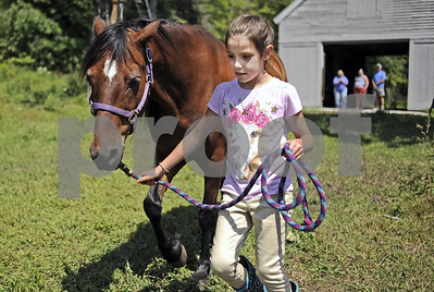 Robert Layman / Staff Photo  Rian Stevens walks her training horse Ryan back to the pasture after a lesson at the Reinbow Riding Center in Shrewsbury Thursday afternoon.