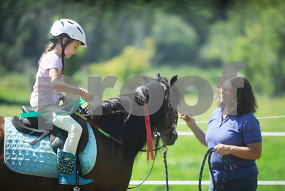 Rian secures a ribbon to her horse's rein.
