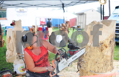 "Robert Layman / Staff Photo  Chainsaw artist Stephanie Jones, of Brantrock, MA, shapes a bear statue into a piece of Vermont-logged white pine during a  live carving demonstrations at the Vermont State Fair Friday afternoon. Jones and her partner Kevin Black, not pictured, have done 18 statues of bears and other wild animals since opening day and said the fair has been a positive experience despite the rain Friday. ""I've been at state fairs during Hurricanes,"" Black said. ""If you think its going to be bad, then it will be,"" he said."